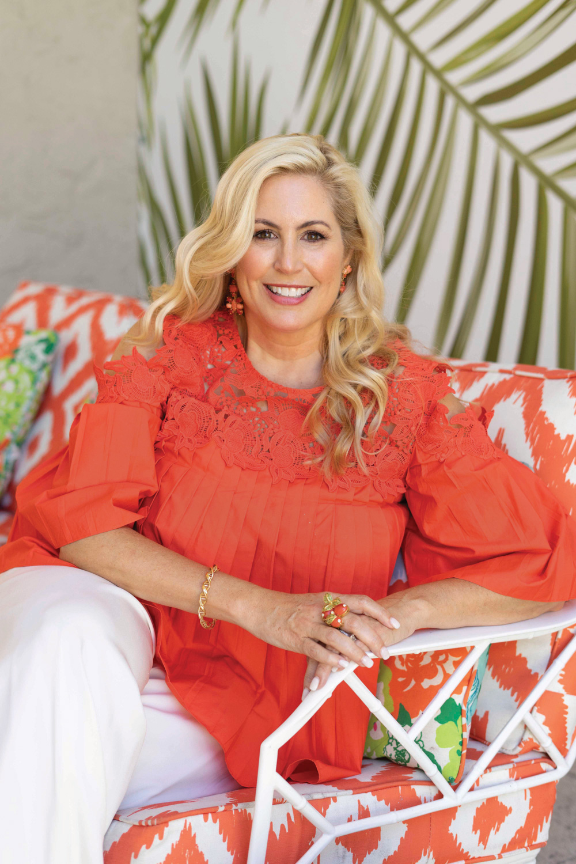 Portrait of designer Carla Fonts Hrncir in a bright orange top