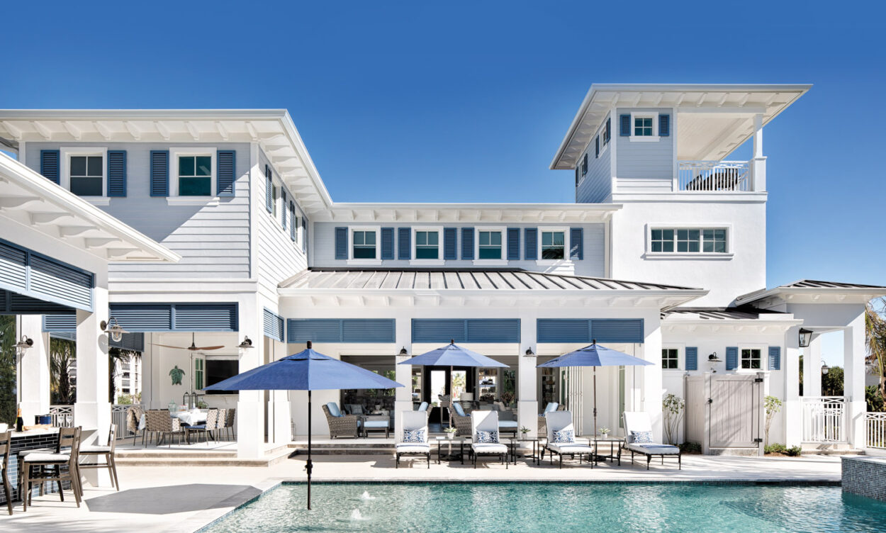 back pool area of two-story gray-and-blue residence
