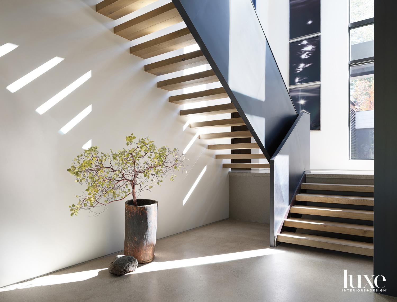 A staircase has a ribbon-like metal stair rail.