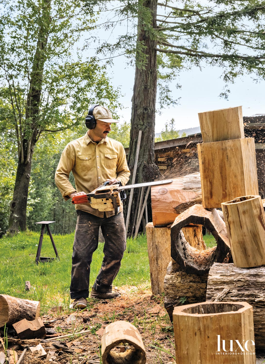 A woodworker uses a chainsaw to shape his creations.