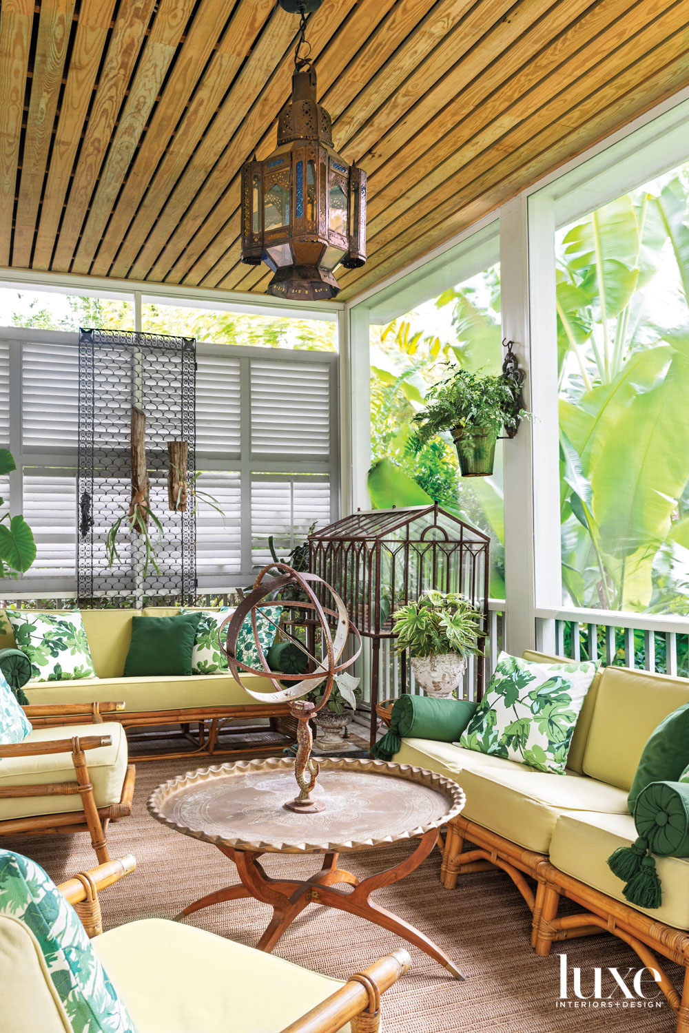 Screened-in porch with yellow sofas, green pillows, a hanging lantern and several live plants