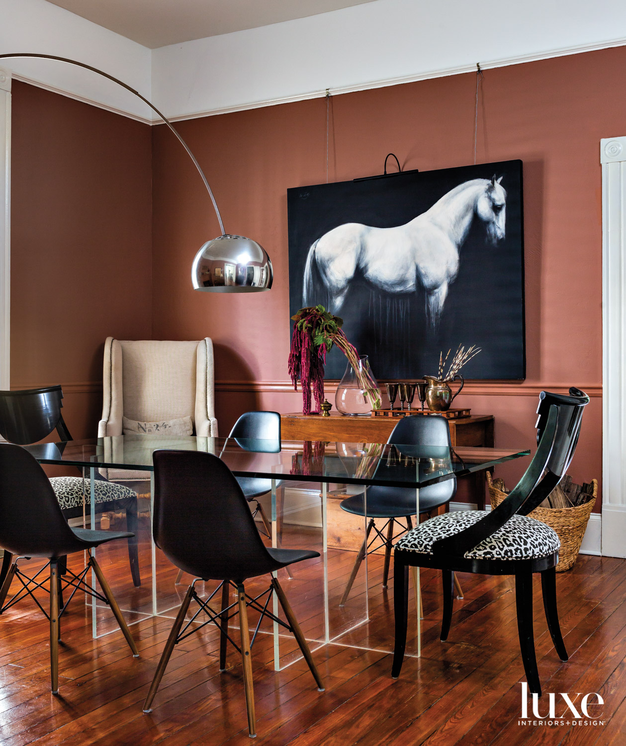 Dining room with terra cotta walls, modern dining table, arc lamp and large equine artwork