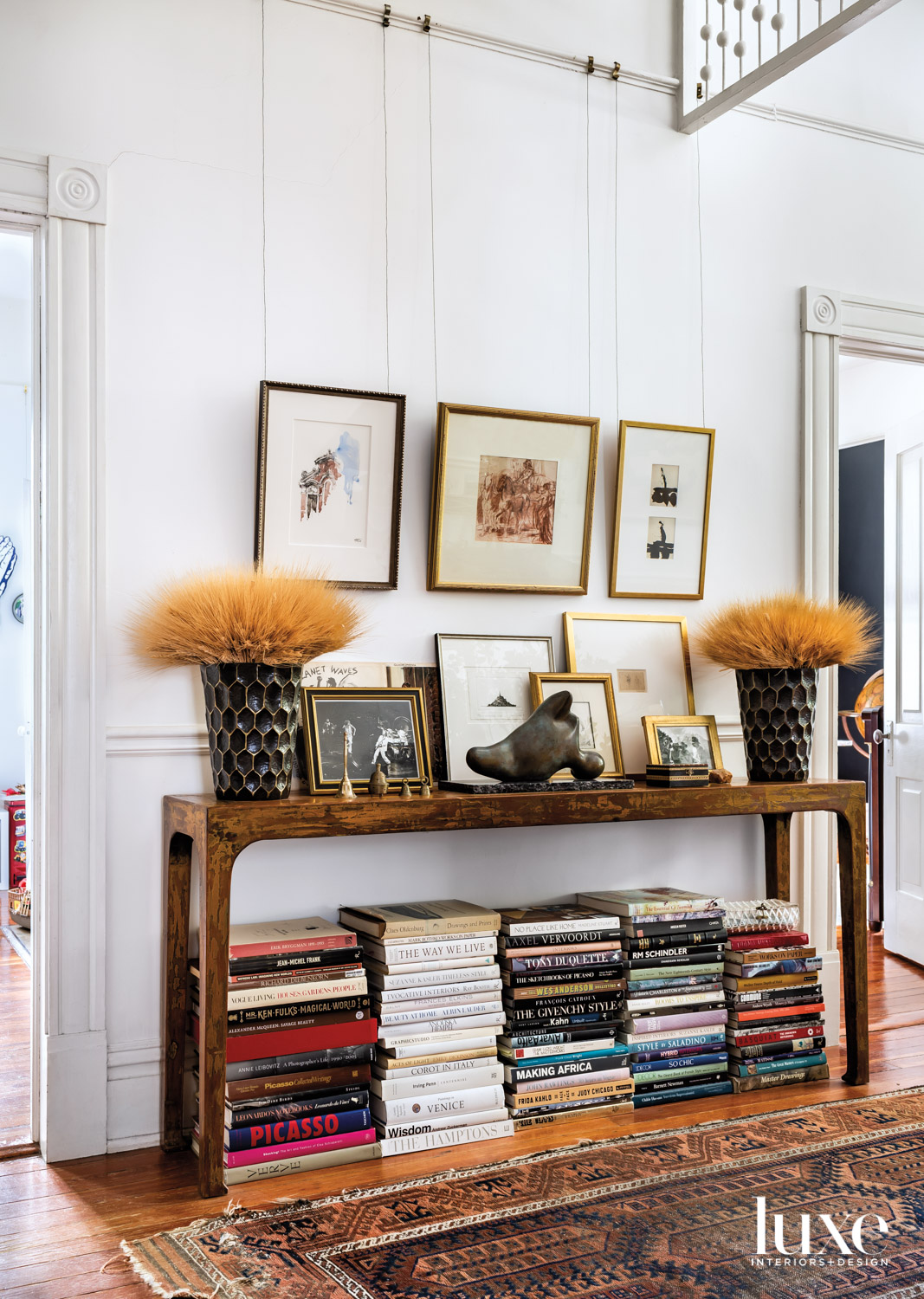 Wooden console table with lots of framed artwork and books