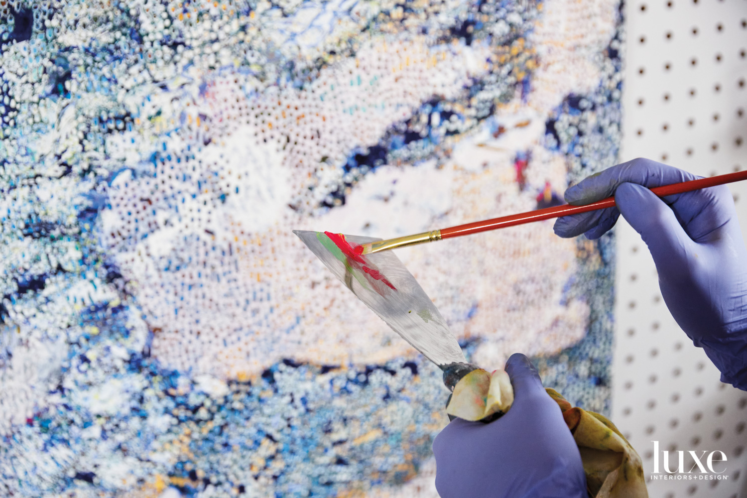 A paint brush picks up red paint from a palette knife