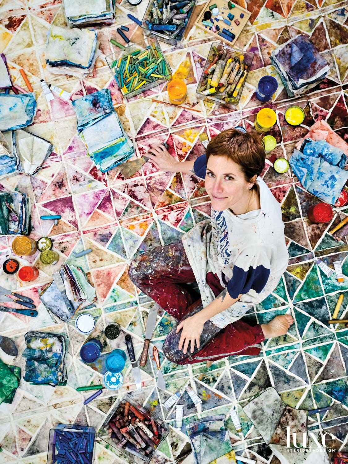 Woman sitting on a quilt with paints and tools surrounding her