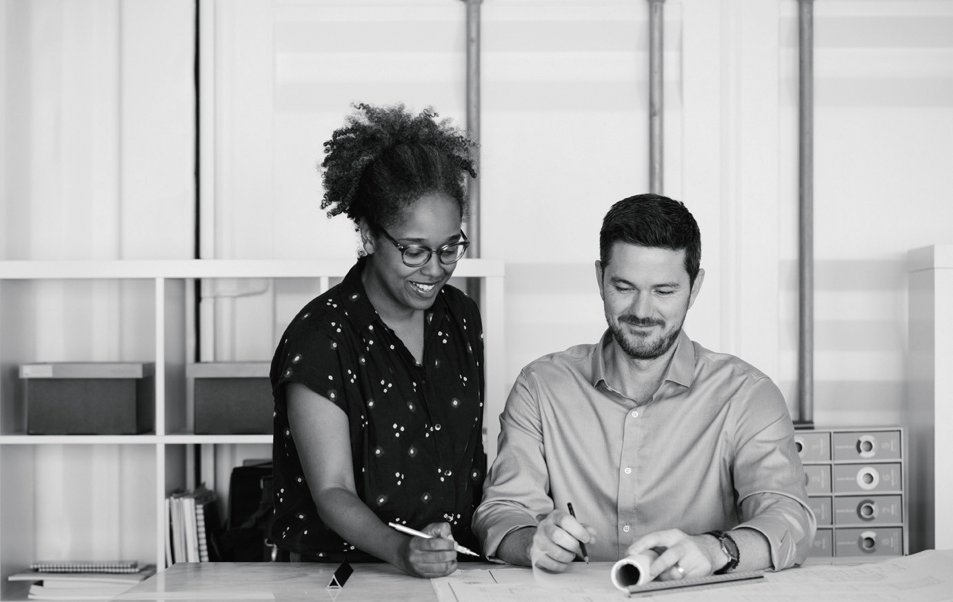 A woman and man drawing together at a desk
