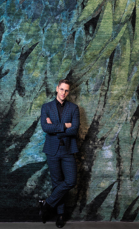 Designer in front of a rug