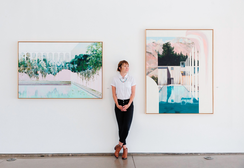 Artist standing between two watercolor landscape paintings.