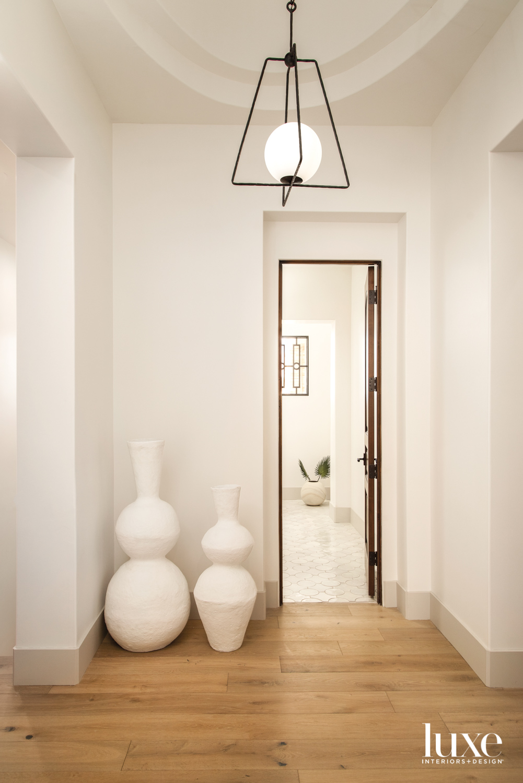 An entryway with hardwood floors,...