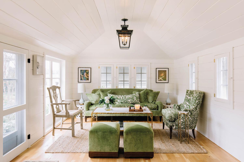 white garden house with velvet green sofa and seating