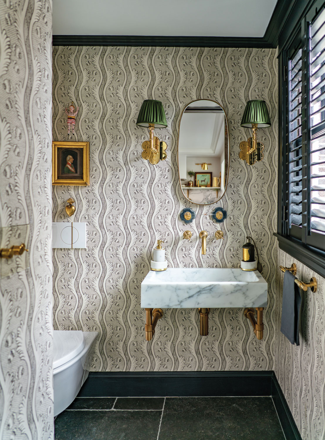 bathroom with gray floral wallpaper and brass details