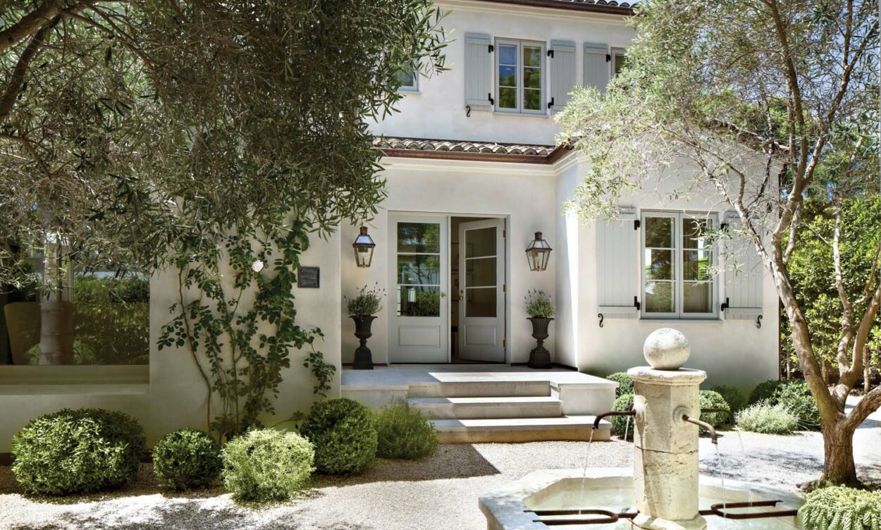 Front entrance to a French Provincial style home with a fountain at the front. House is painted white with blue shutters