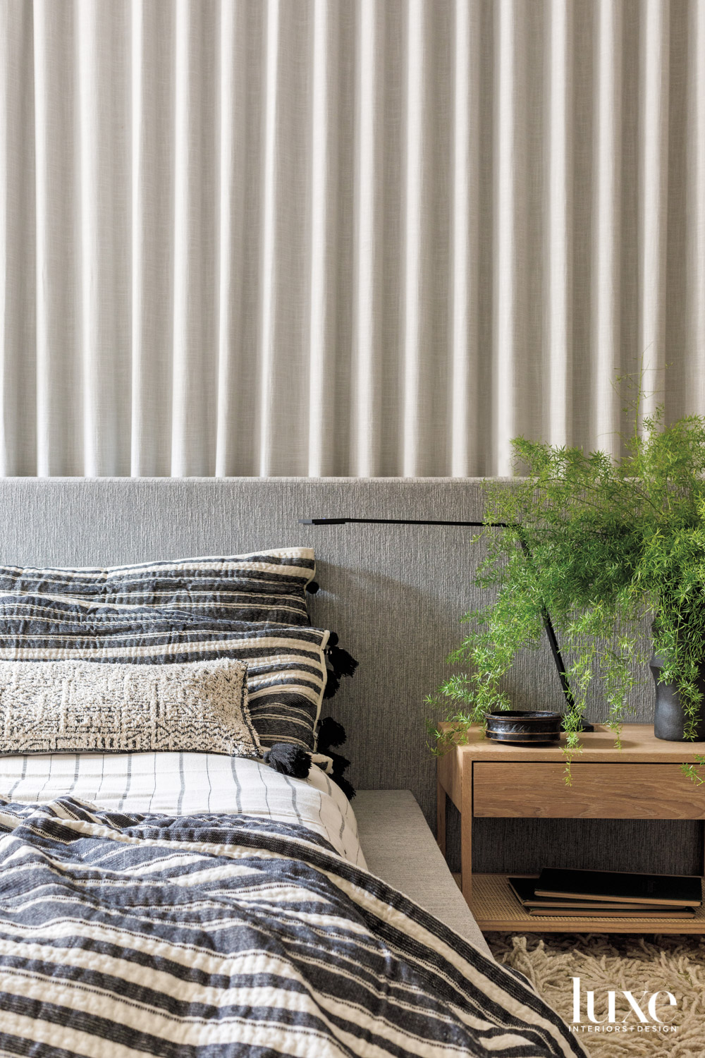 A gray upholstered bed with...