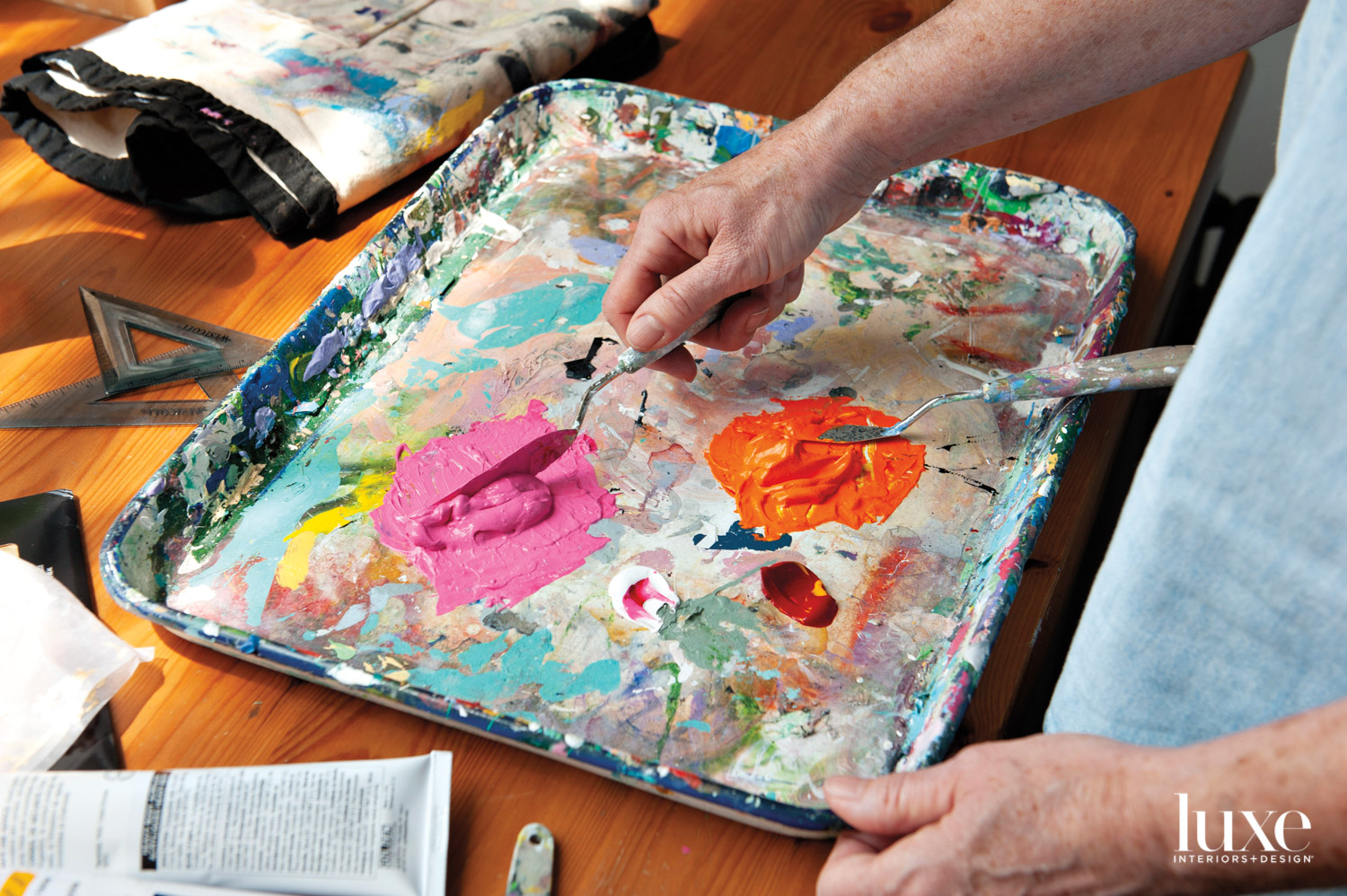 A hand mixing paint on a tray.