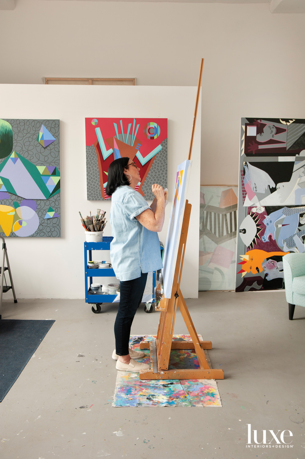 An artist in her studio working on a painting.