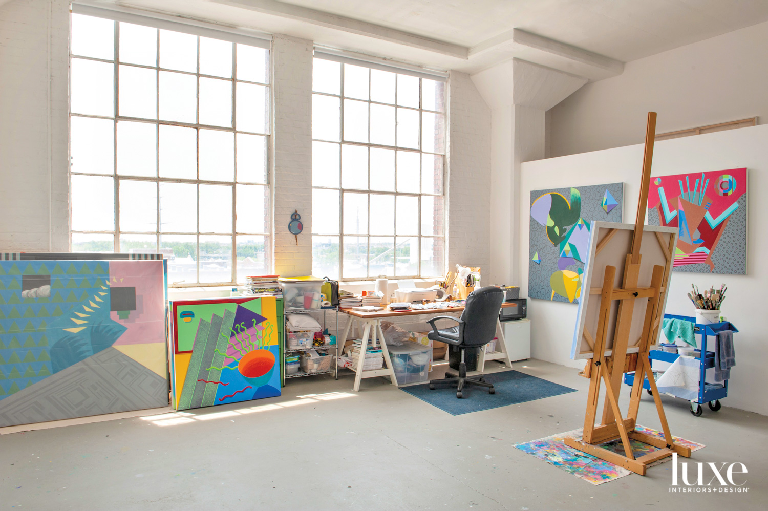 An art studio with large windows. There are multiple colorful hanging and leaning on the walls.