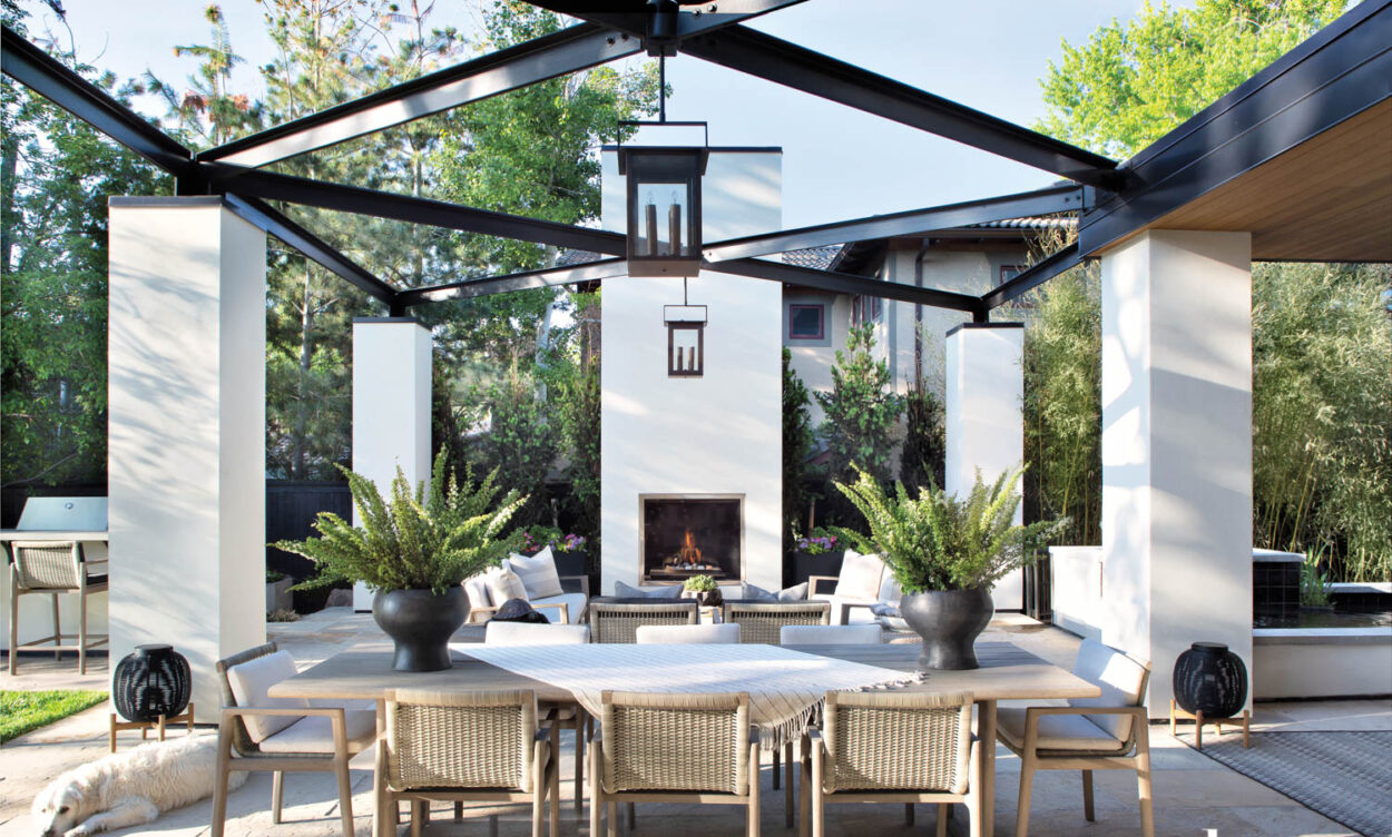An outdoor dining room and lounge has metal trusses overhead.