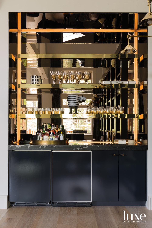 A bar has brass-toned mirror...