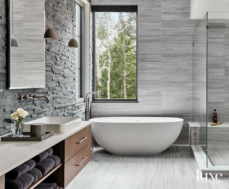 main bathroom with concrete pendant and white soaking tub