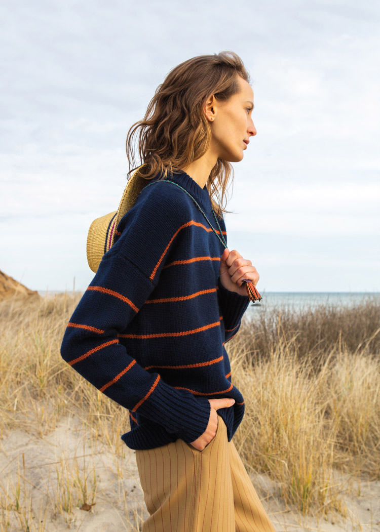 woman on beach in navy and red striped sweater