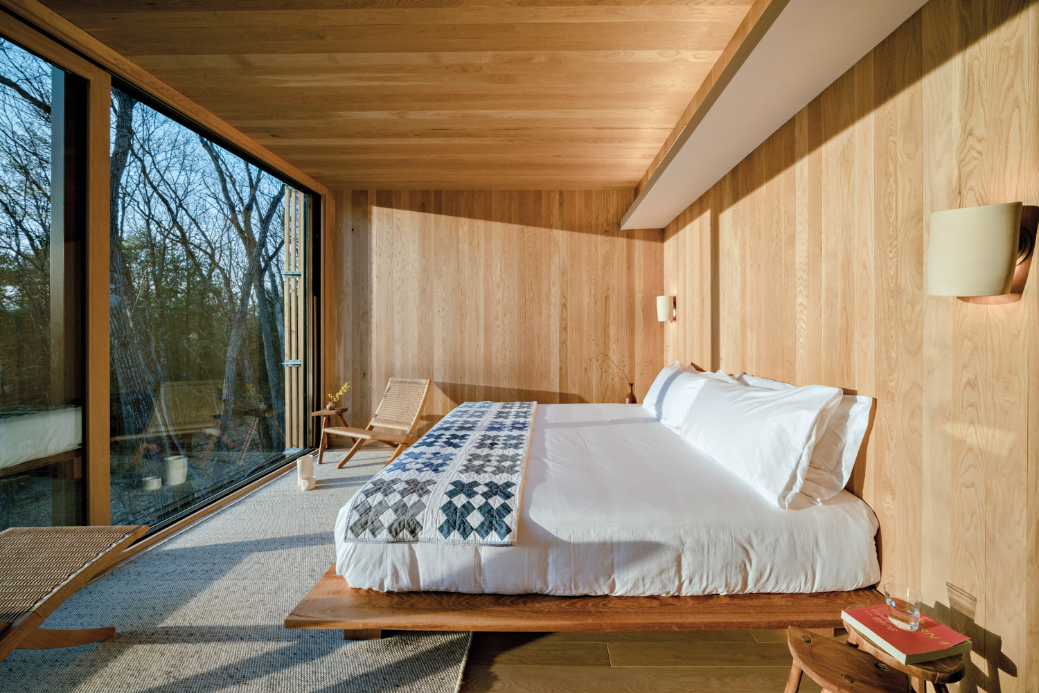 White bed in wood-clad cabin with a large glass window