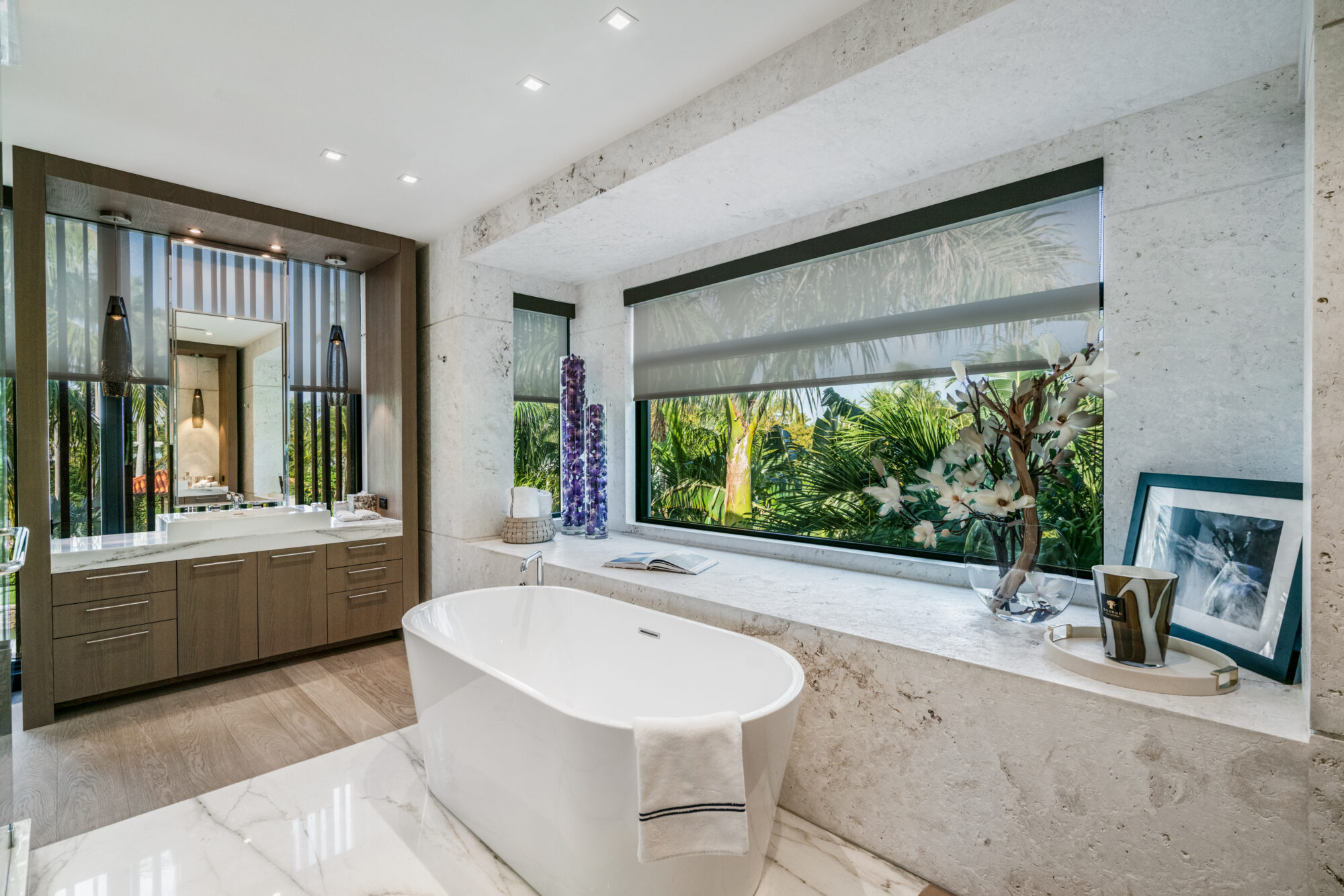 bathroom with freestanding tub and natural stone surfaces in