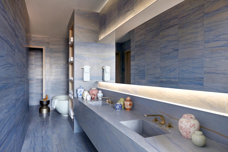 Bathroom clad in dramatic, blue-veined stone