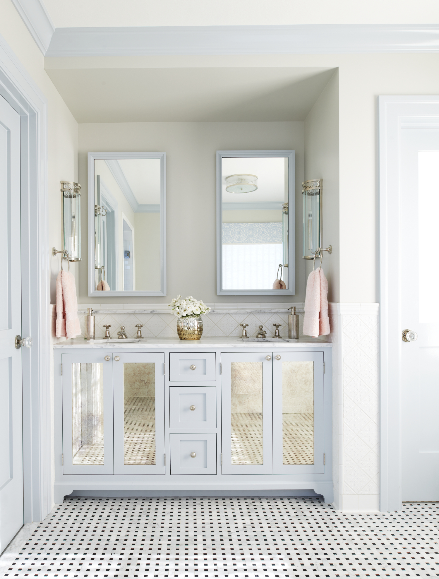 Bathroom vanity in soft pastels with mirrored cabinet fronts