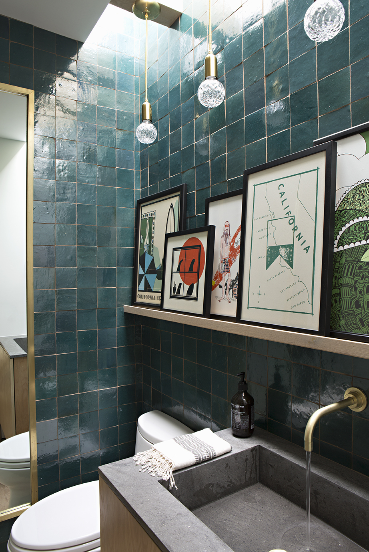 Bathroom with handmade teal wall tiles and ledge of artworks.