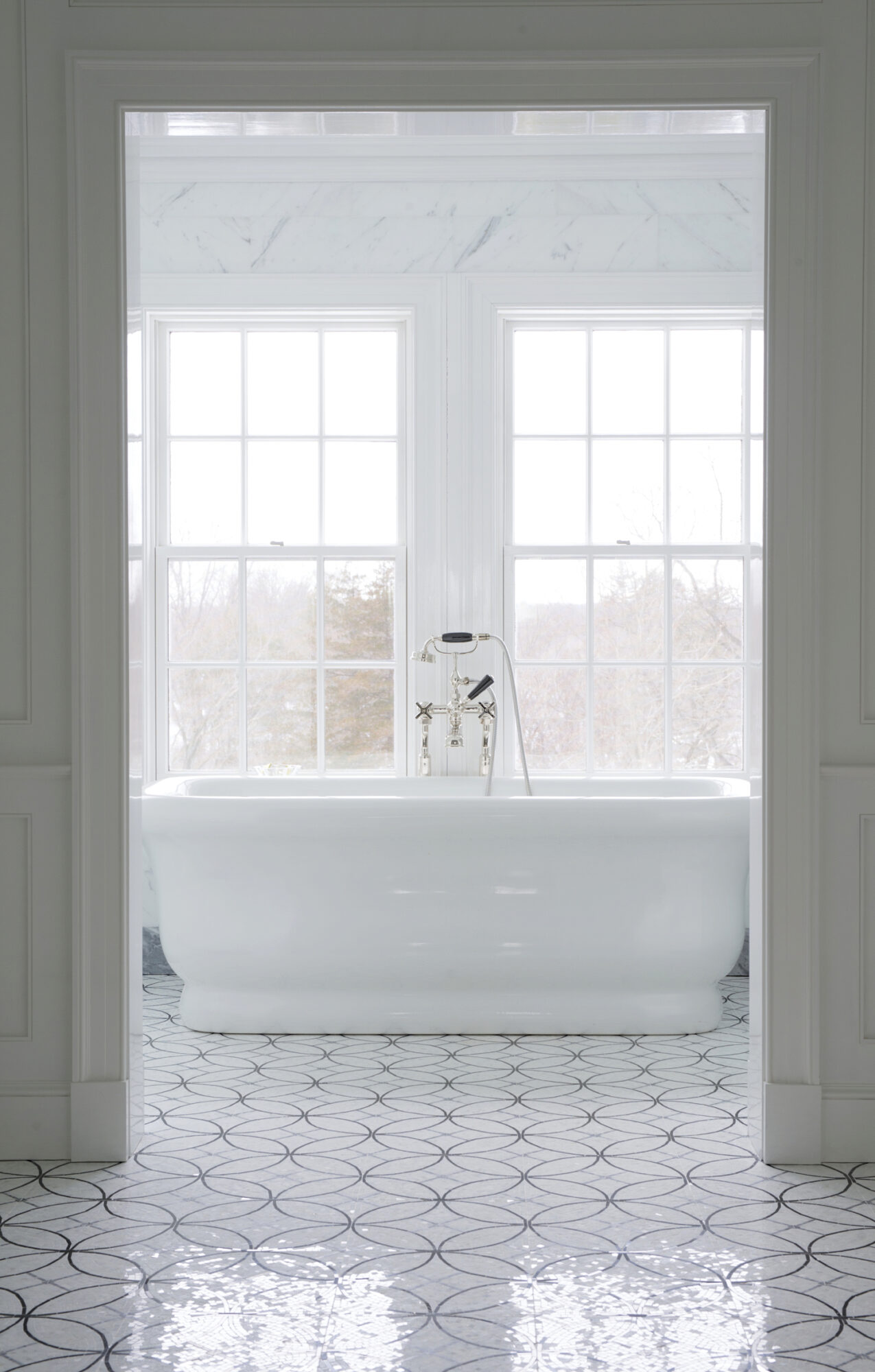 A sunlit bathroom with a standalone tub and large windows