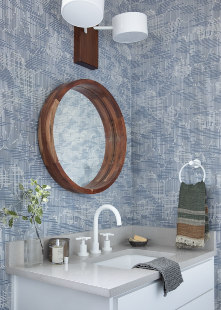 Blue wallpapered bathroom with white faucet