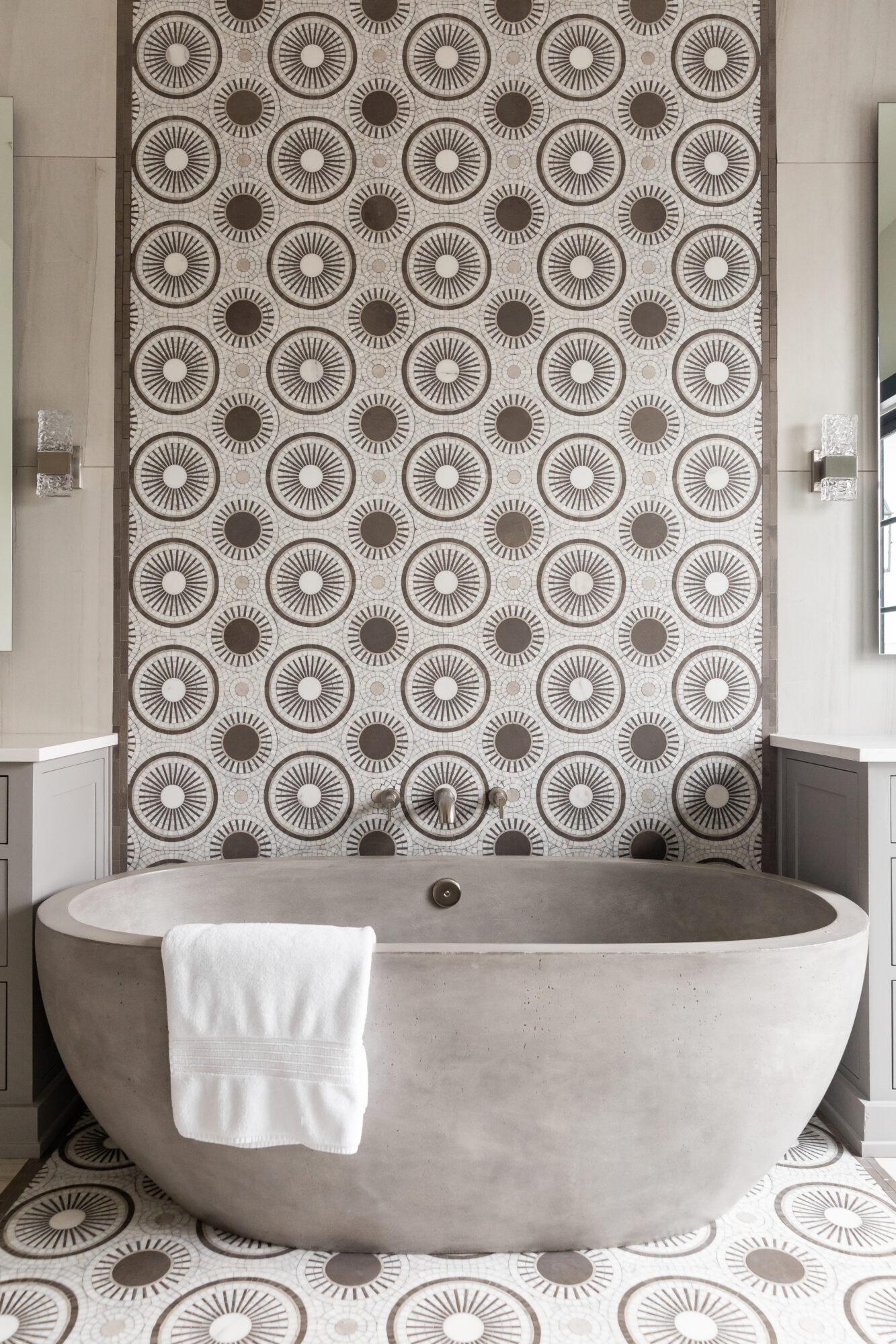 free standing gray stone tub with tile backsplash